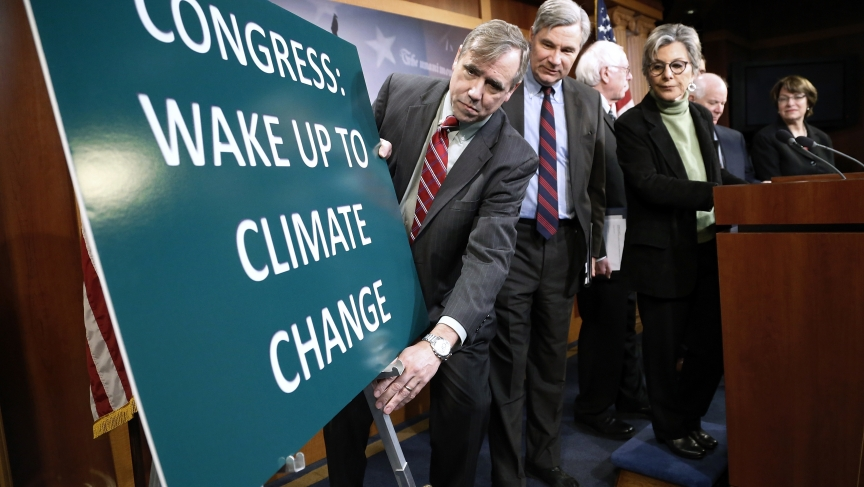 US Senator Jeff Merkley (D-Ore.) adjusts a sign at the start of a news conference led by Senator Barbara Boxer (D-Calif.) to draw attention to climate change in January 2014.