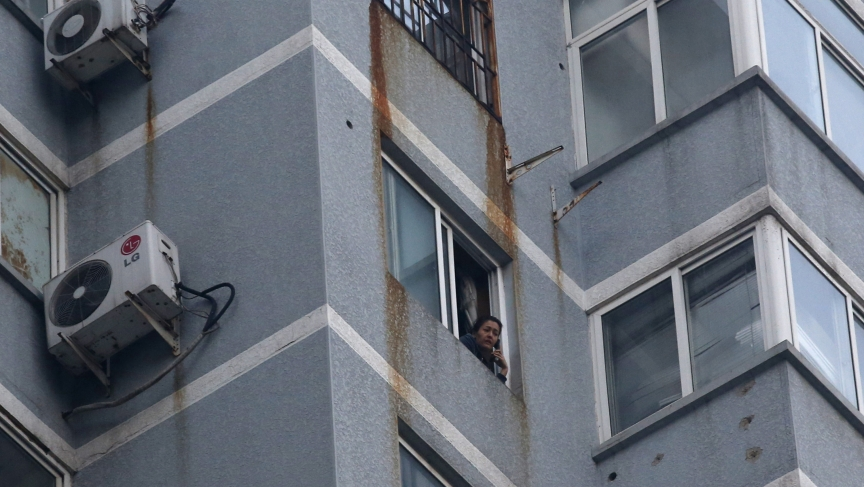 Guzailai Nu'er, the wife of Ilham Tohti, looks out the window of her house in Beijing as she does an interview over the phone with Reuters on January 17, 2014. Nu'er has been prevented from leaving by Chinese police.