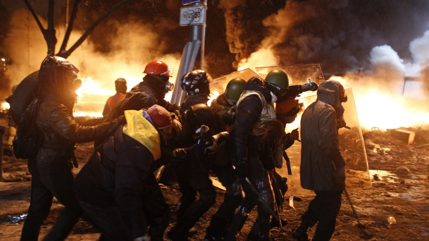 Pro-European protesters take cover behind shields during clashes with riot police in Kiev January 22, 2014. Ukraine opposition leaders said on Wednesday there had been no concrete results from their talks with President Viktor Yanukovich to end weeks of s