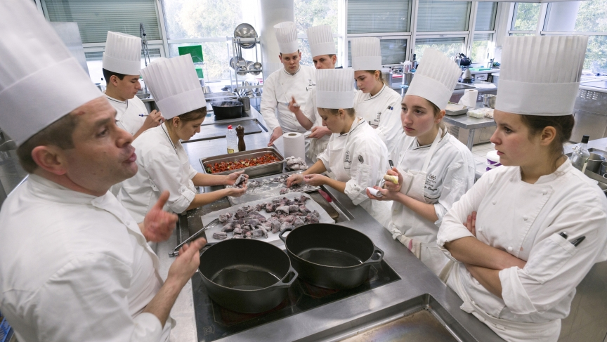 Students prepare food during a class by French chef Eric Cros (left) at the Institut Paul Bocuse.