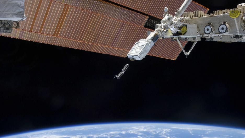 A robotic arm holds a CubeSat