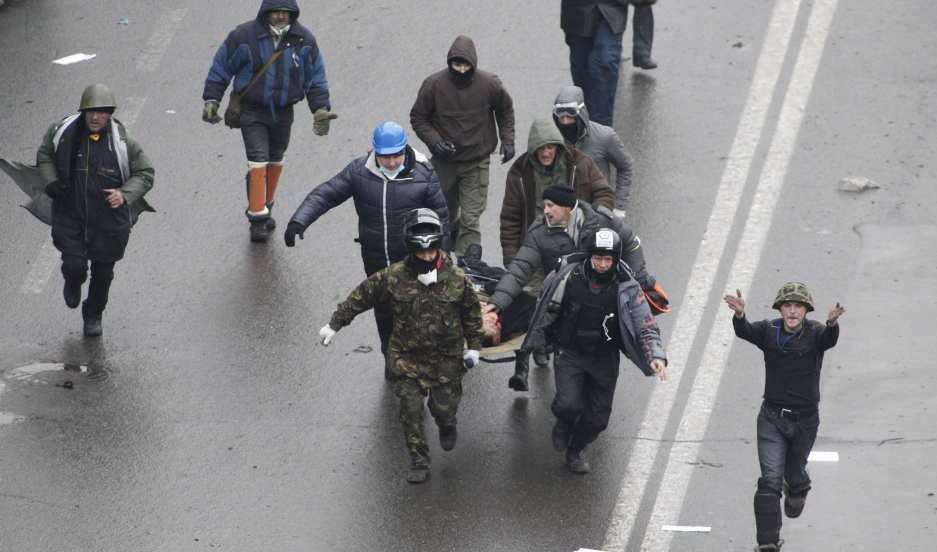 Anti-government protesters run with an injured man on a stretcher in downtown Kiev, February 20, 2014.