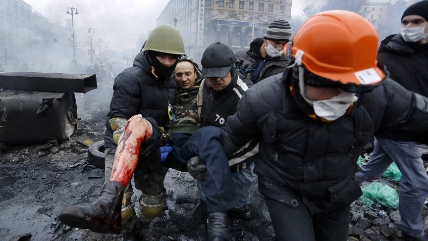 Anti-government protesters carry a man with a bullet wound on his leg during clashes with riot police in Independence Square in Kiev, February 20, 2014.