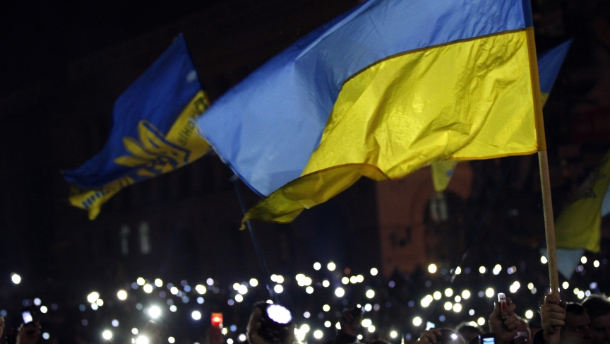 Anti-government protesters light torches and mobile devices in Kiev's central Independence Square. The protesters refuse to leave the streets, despite a deal between political leaders.