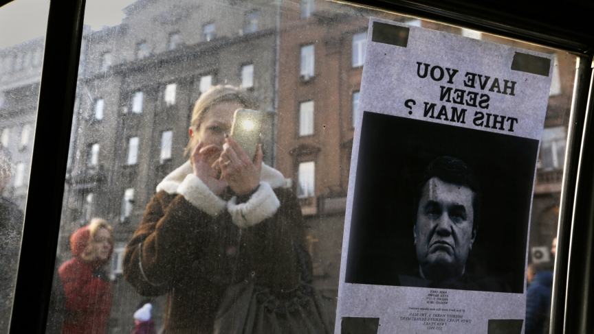 "A woman takes photos of a ""Wanted"" notice for fugitive Ukrainian President Victor Yanukovich, plastered on the window of a car used as a barricade, near Kiev's Independent Square February 24, 2014."