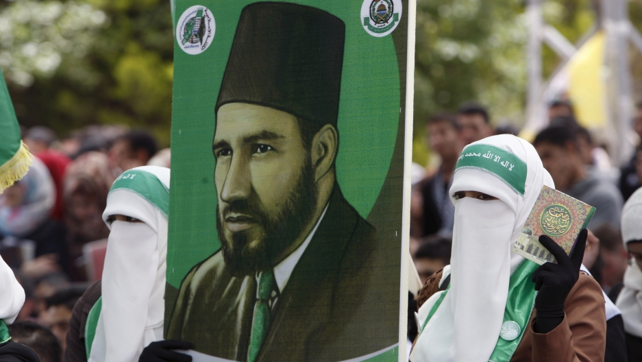 Palestinian students supporting the  militant group Hamas, an organization that's ideologically linked to the Muslim Brotherhood, hold a poster depicting Hassan Al-Banna, the Muslim Brotherhood founder, during an election campaign for students' council at