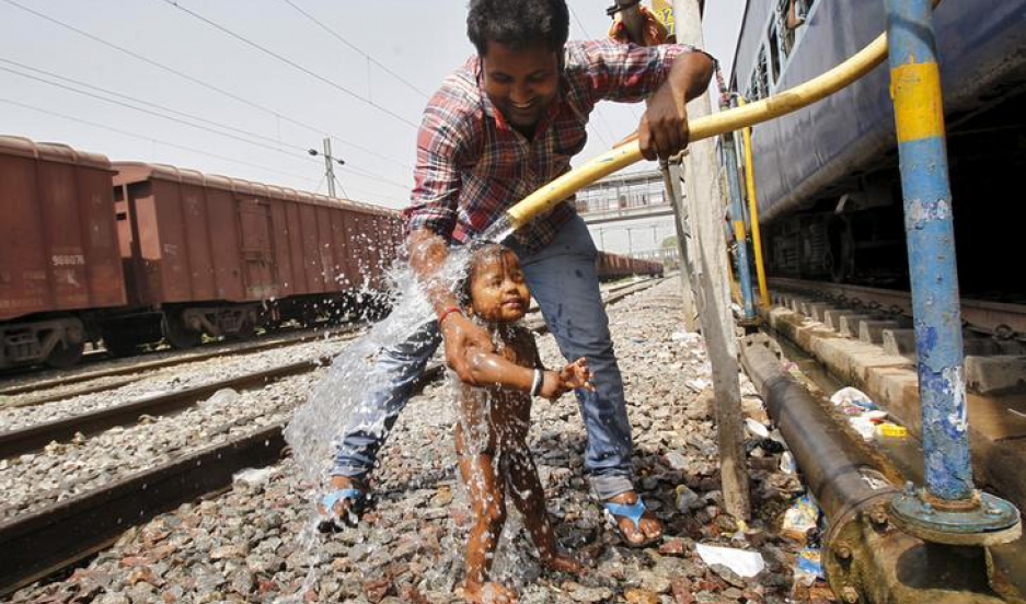 A passenger cools off a child using a pipe that supplies water to trains at a railway station on a hot summer day in the northern Indian city of Allahabad April 23, 2015.