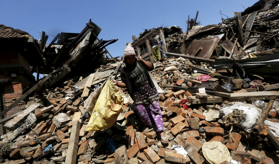 A woman carries her belongings as she walks over a collapsed house in Bhaktapur, Nepal, on April 27, 2015.