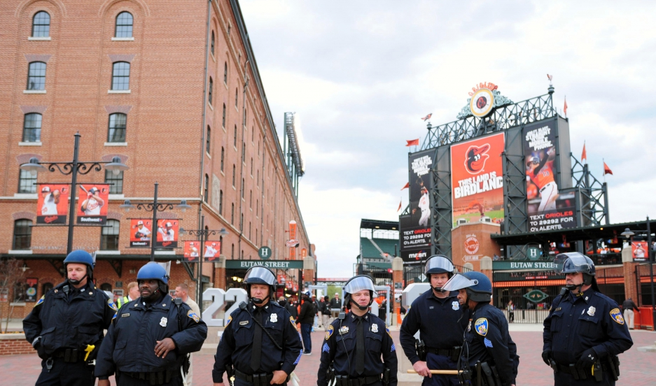 Baltimore police officers stand outside of Oriole Park at Camden Yards prior to the cancellation of a game between the Chicago White Sox and Baltimore Orioles on April 27, 2015.