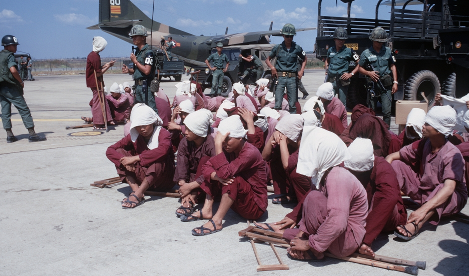 Viet Cong prisoners sit on a tarmac in Vietnam in 1973, under watch by South Vietnamese military police.