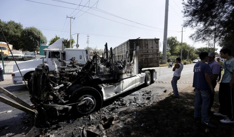 Men stand next to the wreckage of a tractor-trailer set ablaze by members of a drug cartel in Guadalajara May 1, 2015.