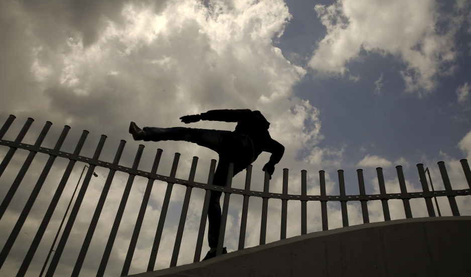 An African immigrant jumps over a fence into a ferry terminal in the western Greek town of Patras on April 28, 2015.