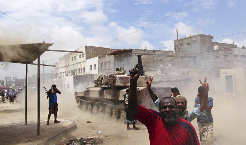 Southern Popular Resistance fighters react as one of their tanks fire at a Houthi position during fighting in Yemen's southern city of Aden