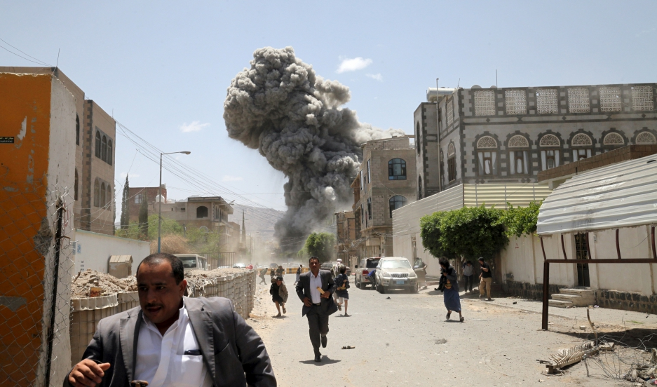 People flee as smoke billows after air strikes hit the house of Yemen's former President Ali Abdullah Saleh in Sanaa May 10, 2015