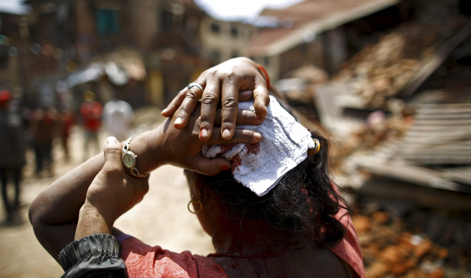 An injured woman walks toward a hospital soon after an earthquake struck Sankhu, Nepal, on May 12, 2015. The 7.3-magnitude quake killed more than two dozen people in Nepal and neighboring states.
