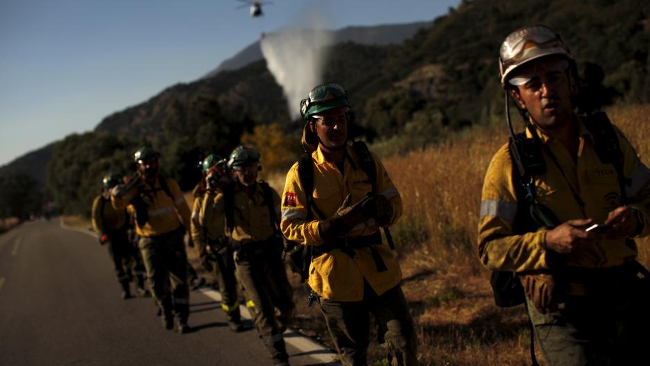 firefighters walk along a road