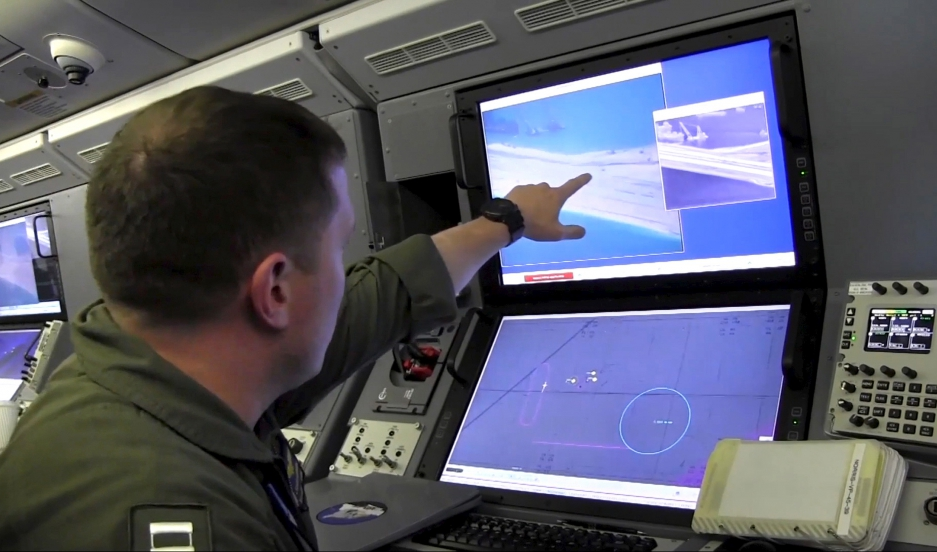 A U.S. Navy crewman aboard a P-8A Poseidon surveillance aircraft views a computer screen purportedly showing Chinese construction on the reclaimed land of Fiery Cross Reef in the disputed Spratly Islands in the South China Sea in this still image from vid