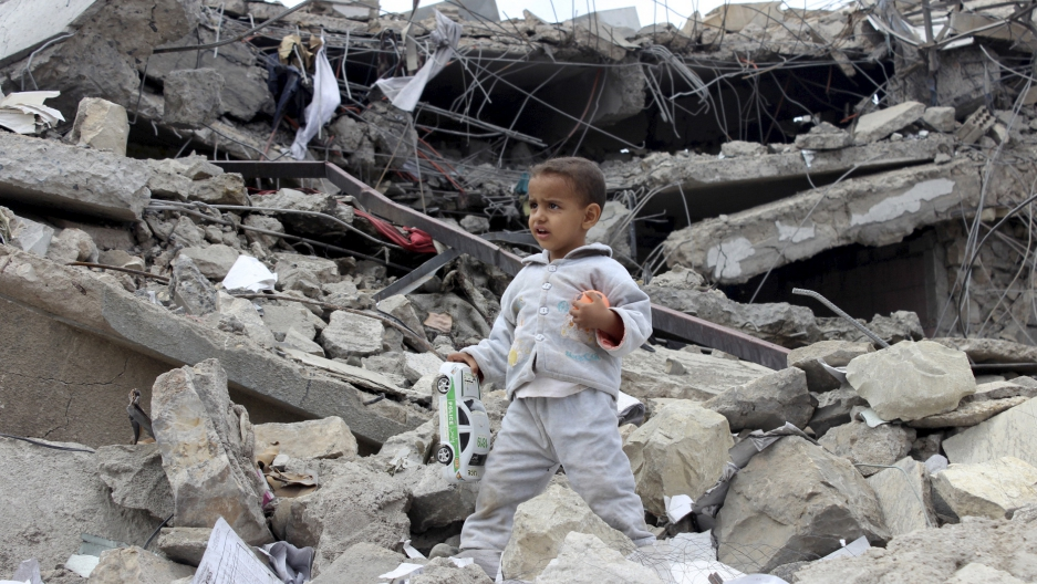 boy walks as he collects toys from the rubble of a house destroyed by a recent air strike in Yemen's northwestern city of Saada