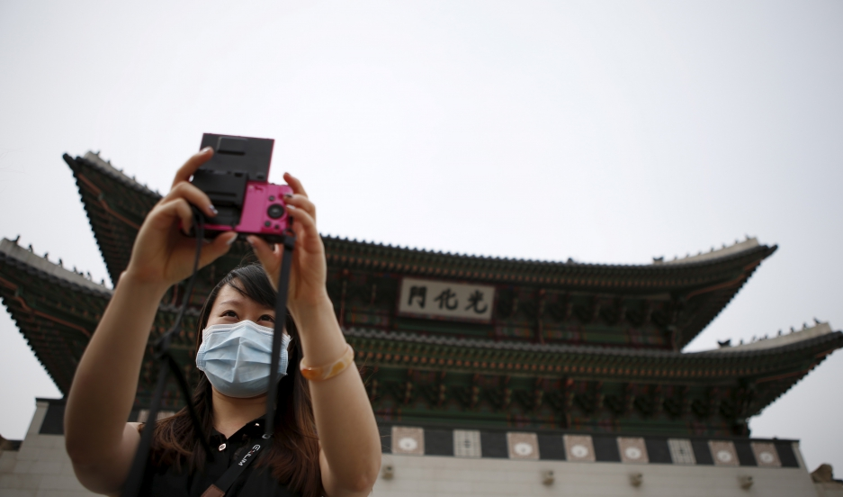 Chinese tourist wearing a mask to prevent contracting Middle East Respiratory Syndrome (MERS) takes a selfie in front of the main entrance of the Gyeongbok Palace in central Seoul, South Korea on June 4, 2015.