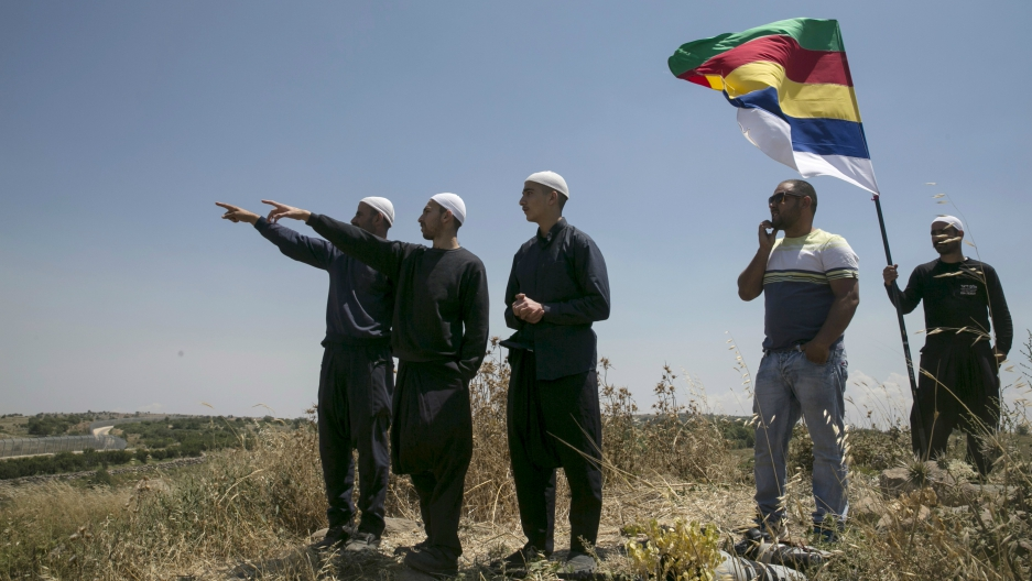 Members of the Druze community watch the fighting in Syria's civil war, next to the border fence between Syria and the Israeli-occupied Golan Heights, near the Druze village of Majdal Shams, June 16, 2015.