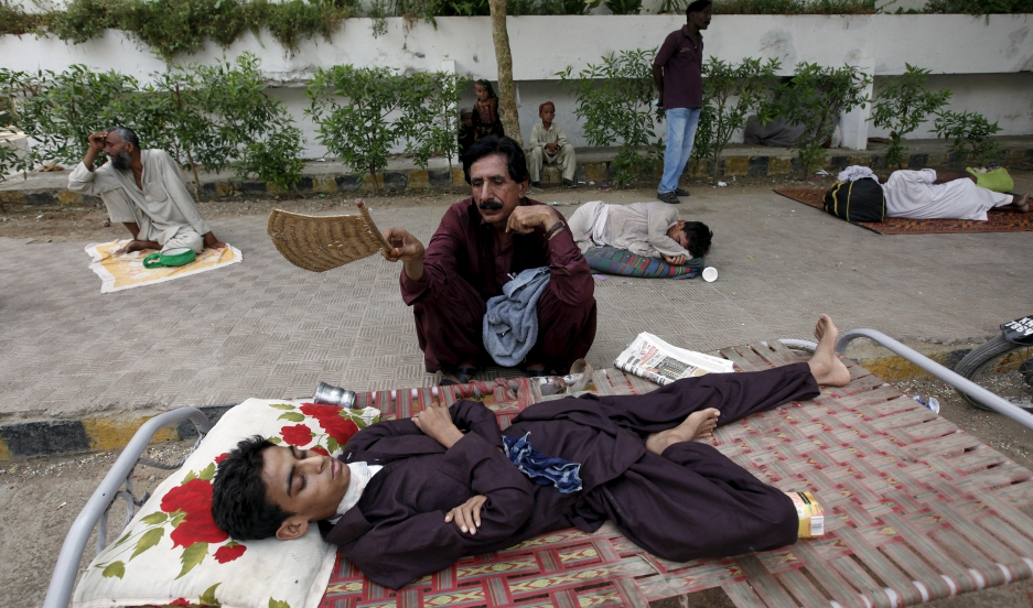 A man uses a hand-held fan to cool down his son, while waiting for their turn for a medical checkup, outside Jinnah Postgraduate Medical Centre (JPMC) during intense hot weather in Karachi, Pakistan, June 23, 2015.