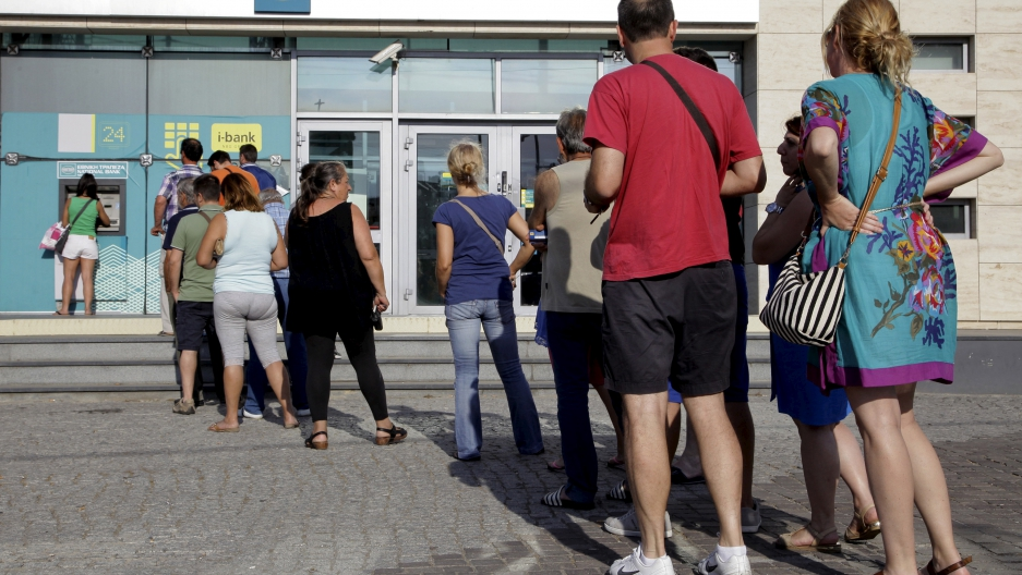 People line up to withdraw cash from an ATM in Greece