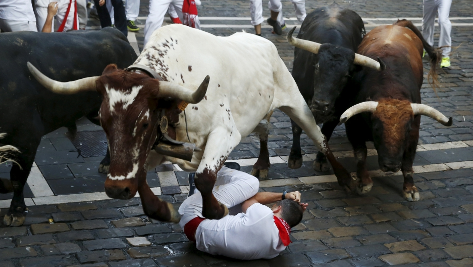 Steer jumps over a runner during the running of the bulls in Pamplona