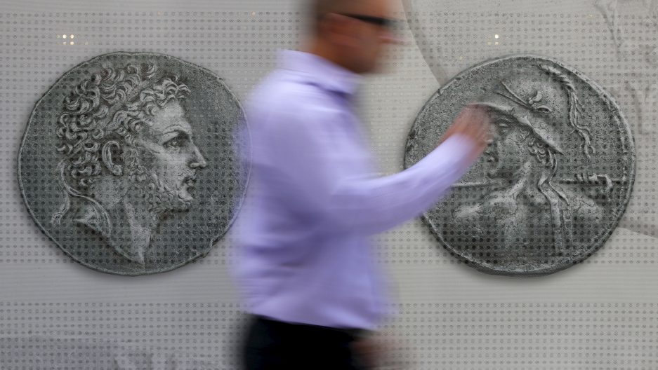 A man walks past pictures of ancient coins in central Athens