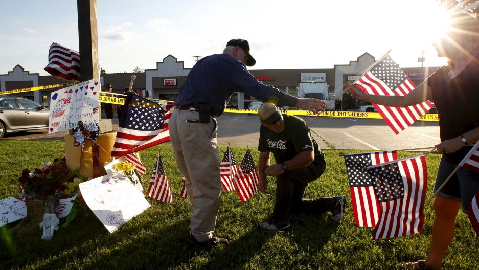 Mourners places flags at a growing memorial in front of the Armed Forces Career Center in Chattanooga, Tennessee on July 16, 2015. Four Marines were killed on Thursday by a gunman who opened fire at two military offices in Chattanooga, Tennessee, before b