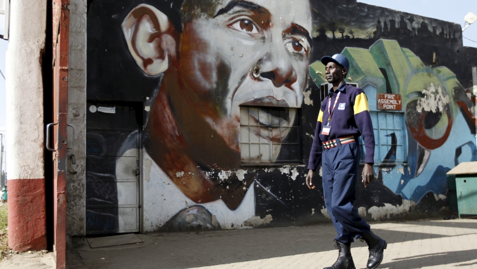 A security guard walks past a wall mural depicting President Barack Obama in Kenya's capital, Nairobi