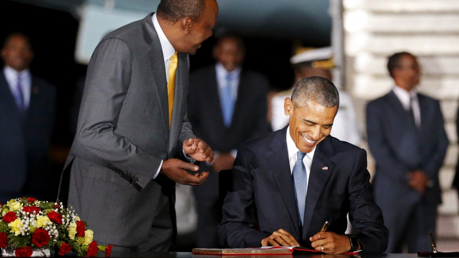 Kenya's President Uhuru Kenyatta (L) looks on as U.S. President Barack Obama signs a guest book as he arrives aboard Air Force One at Jomo Kenyatta International Airport in Nairobi July 24, 2015.