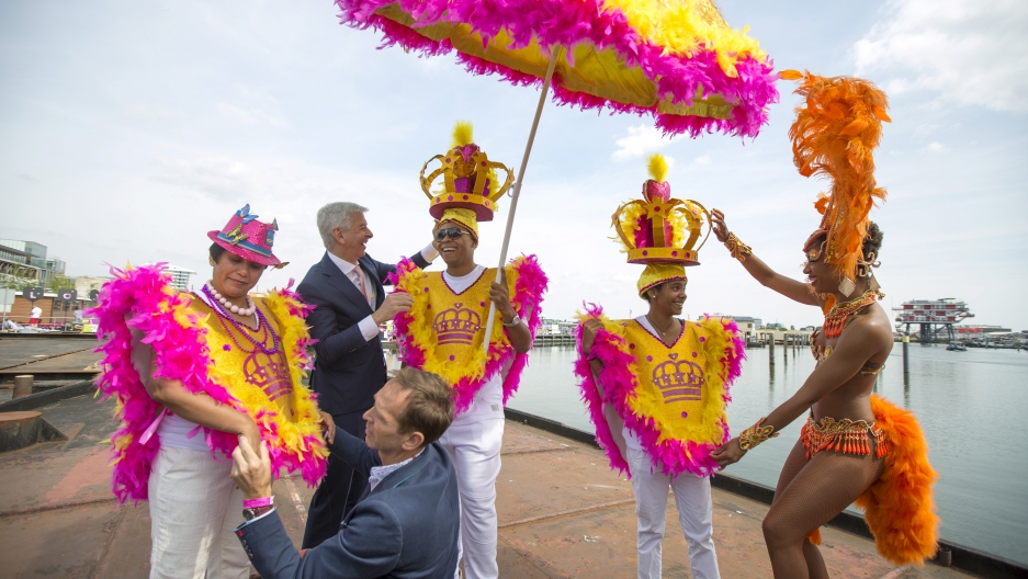 The Netherlands' Minister of Kingdom Relations Ronald Plasterk (2nd L, top) helps adjust costumes of participants from Curacao before their boat leaves for the festival's canal parade in Amsterdam, the Netherlands August 1, 2015.