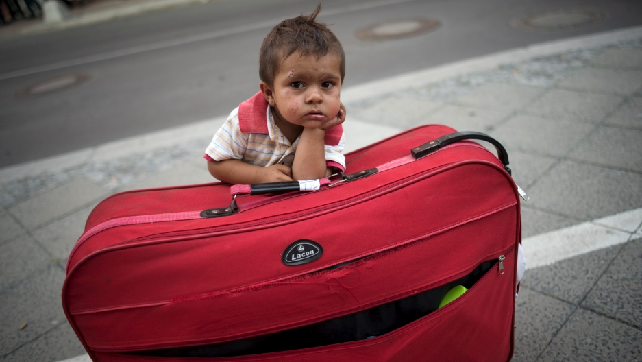 A migrant boy guards his parents' suitcase, as the family waits all day to apply for asylum in Berlin.