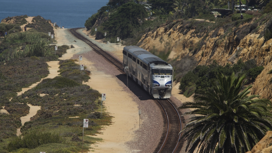 An Amtrak passenger train makes its way along the coastline