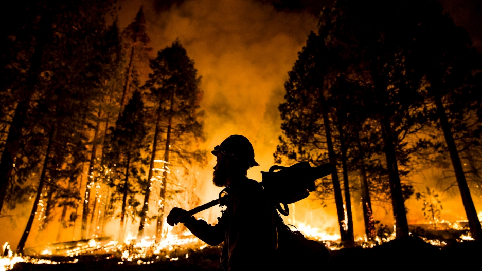 A firefighter watches a controlled burn in Sequoia National Forest, California