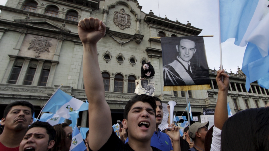 Demonstrators shout as they hold Guatemalan national flags and a picture of former Guatemalan President Jacobo Arbenz, during a protest against Guatemala's President Otto Perez in Guatemala City, Guatemala, August 22, 2015.
