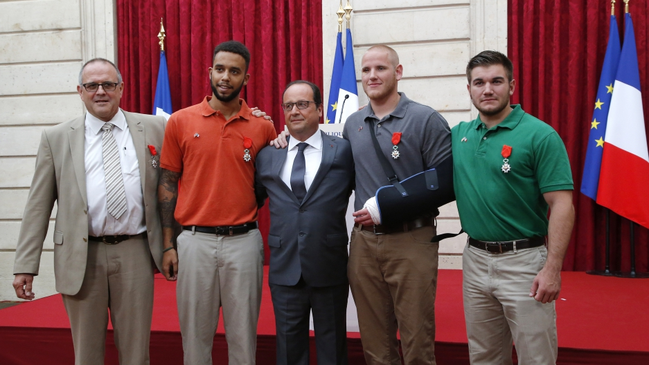 French President Francois Hollande (C) poses with British businessman Chris Norman (L), U.S. student Anthony Sadler (2ndL), U.S. Airman First Class Spencer Stone (2ndR) and U.S. National Guardsman Alek Skarlatos (R) during a ceremony at the Elysee Palace