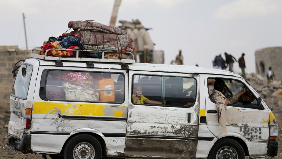 People ride a van as they flee their house near the site of a Saudi-led air strike in Yemen's capital Sanaa August 26, 2015.