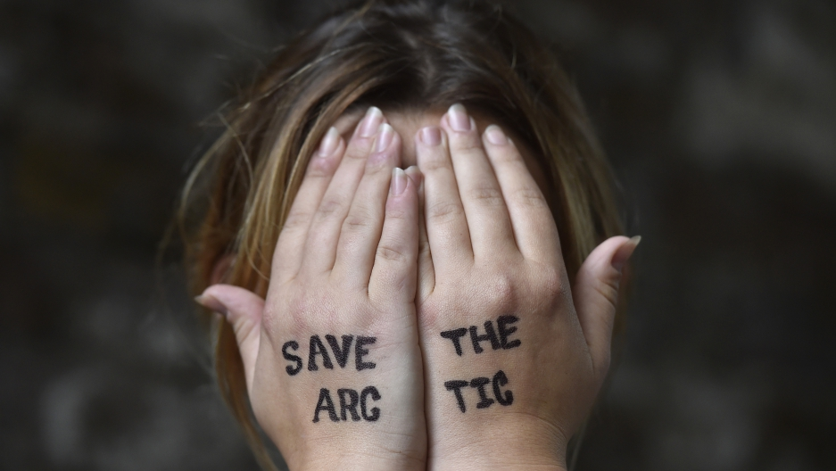 British singer Charlotte Church holds her hands to her face during an environmental protest near the offices of Shell in central London, Britain August 26, 2015.