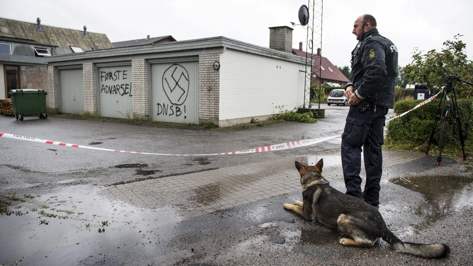 A policeman stands guard in front of the Red Cross asylum center in Lyngbygaard in Trustrup, in the west of Denmark, August 27, 2015.