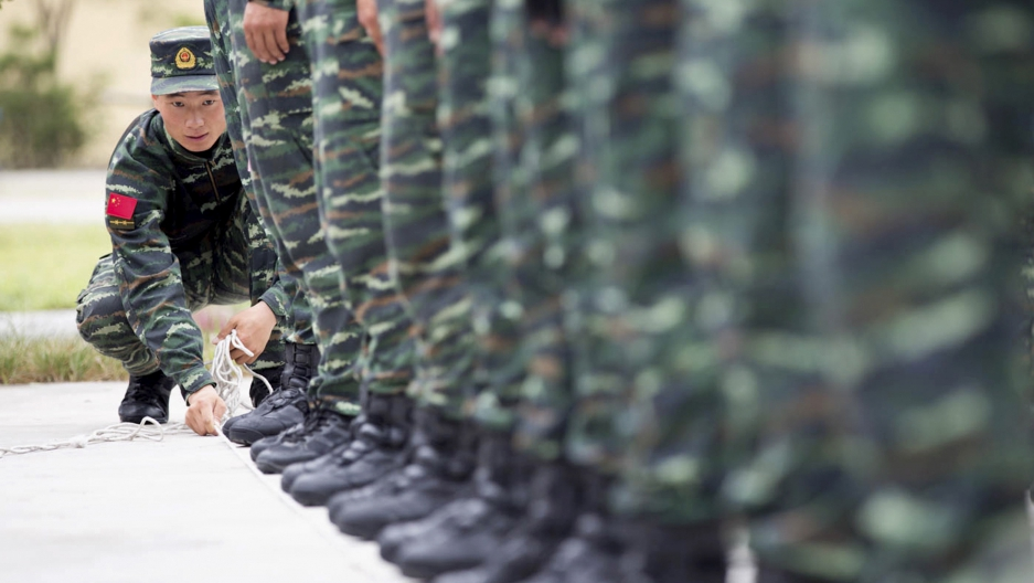 A soldier from China's People's Liberation Army uses a rope to line up other soldiers during a training session for a military parade to mark the 70th anniversary of the end of World War Two, at a military base in Beijing, China, September 1, 2015.