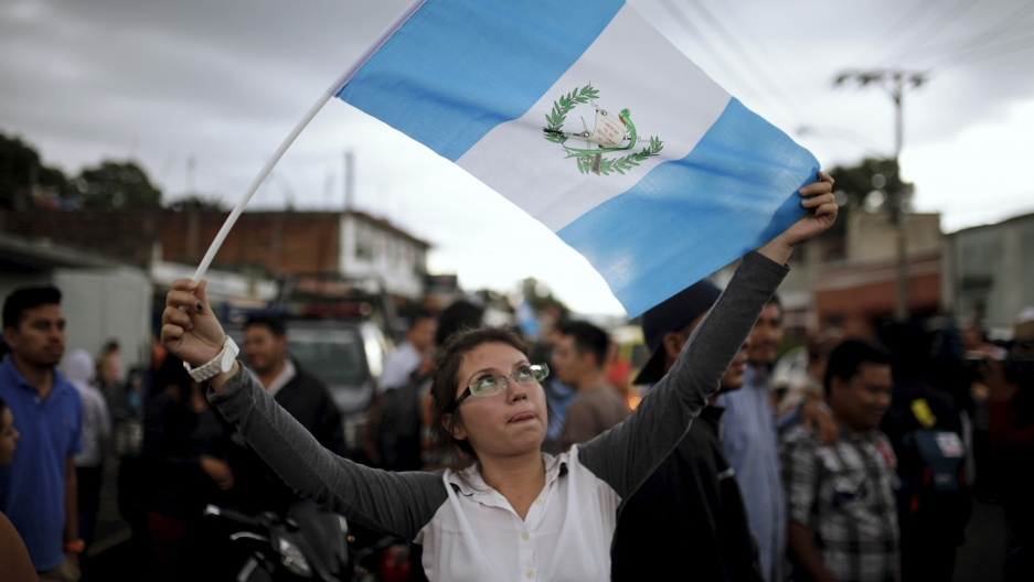 A woman holds a Guatemalan flag and celebrates as Guatemala's former President Otto Perez arrives at Matamoros Army Base, after a hearing at the Supreme Court of Justice, in Guatemala City, September 3, 2015.