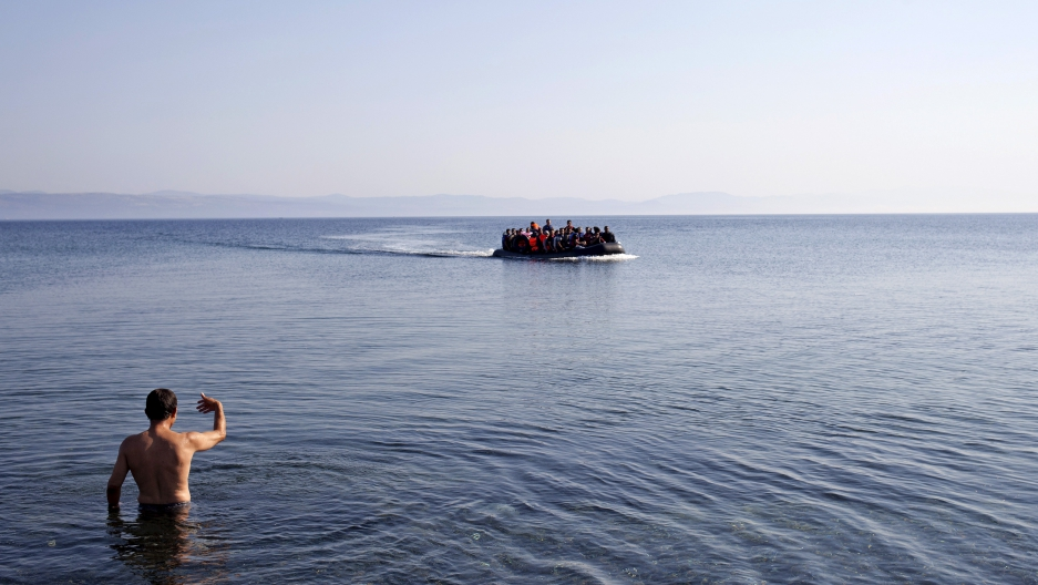 A local man gestures to Syrian refugees on a dinghy approaching the shores of the Greek island of Lesbos, September 4, 2015.