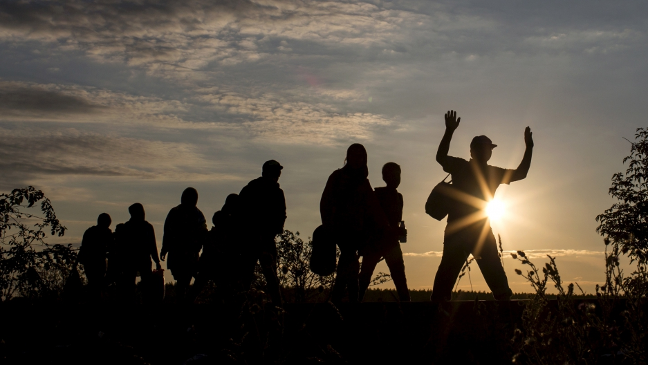 Migrants walk along rail tracks as they arrive at a collection point in the village of Roszke, Hungary, September 8, 2015, after crossing the border from Serbia.