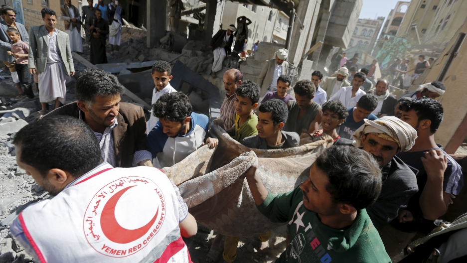 A medic and people carry the body of a boy following a Saudi-led air strike in Yemen's capital Sanaa September 22, 2015.