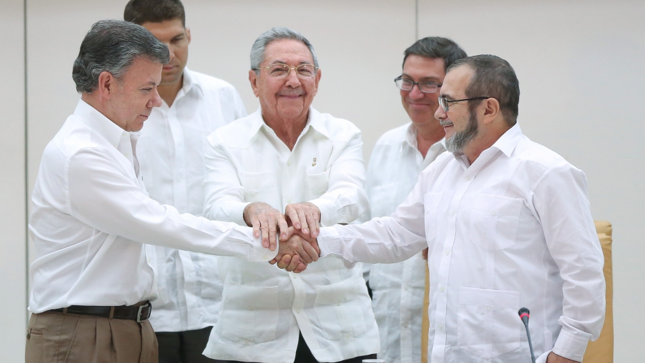 Cuba's President Raul Castro oversees a handshake between Colombia's President Juan Manuel Santos (left) and FARC rebel leader Rodrigo Londono (right), better known by the nom de guerre Timochenko.