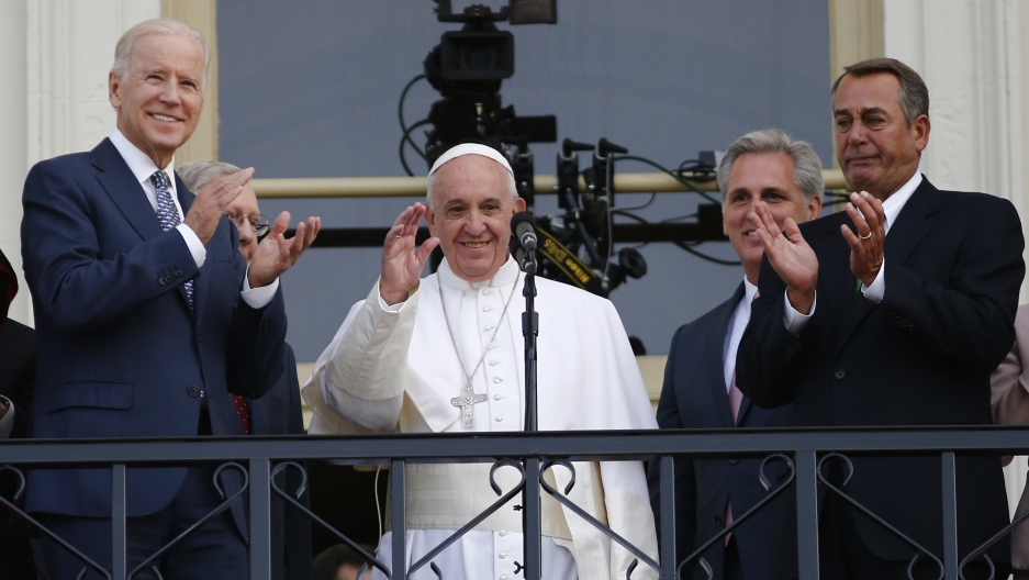 Pope Francis waves to the crowd from the Speaker's Balcony on the West Front of the Capitol as he stands with Vice President Joe Biden (L) and Speaker of the House John Boehner (R) after concluding his address before a joint meeting of the U.S. Congress o
