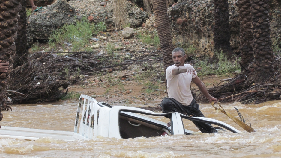 A man gestures as he tries to save a vehicle swept away by flood waters in Yemen's island of Socotra November 2, 2015.