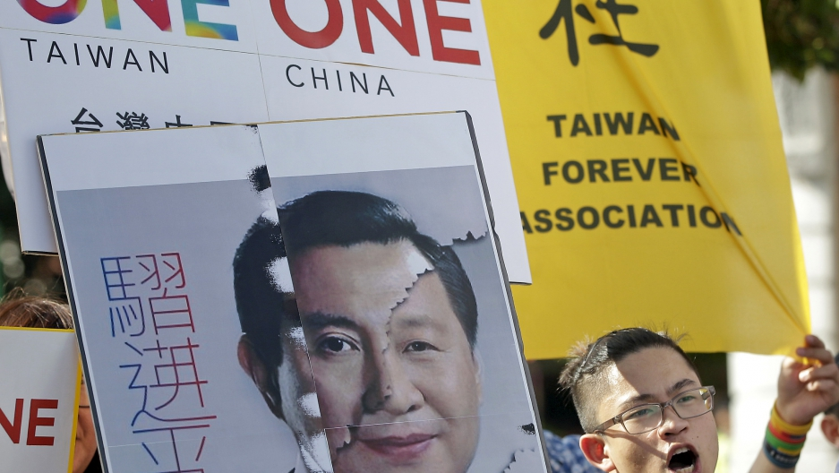 An activist holds a placard showing the merged faces of Taiwan's President Ma Ying-jeou and China's President Xi Jinping, to protest against the upcoming Singapore summit meeting between the two leaders.