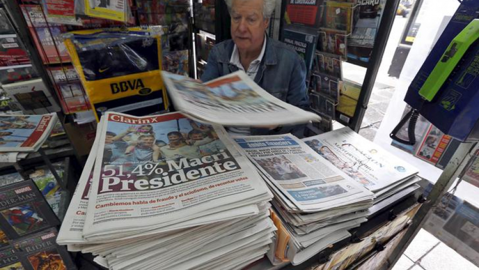 A man sells newspapers printed with the frontpage image of Argentina's president-elect Mauricio Macri in Buenos Aires.